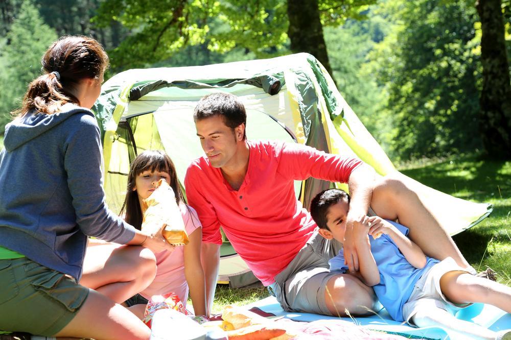 Famile mit Mutter, Vater, Kind vor einem Zelt