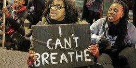 """Demonstrantinnen, sitzend auf dem Boden, eine trägt ein Schild mit der Aufschrift """"I can't breathe"""""""